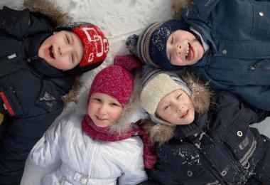 Fire børn ligger i sneen